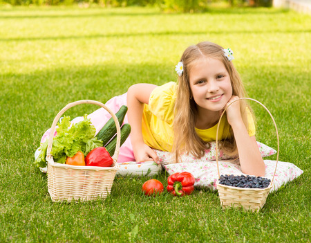 girl lying on green grass with vegetables and berry photo