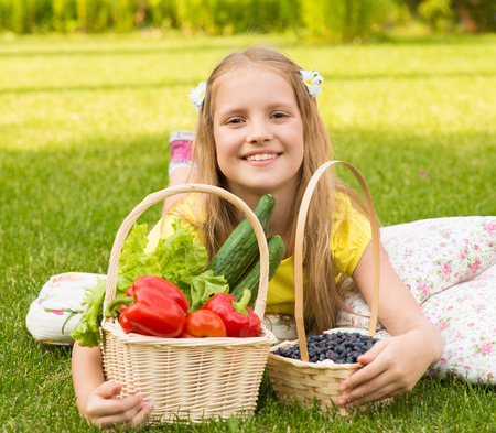 Smiling little girl with vegetables and berry photo