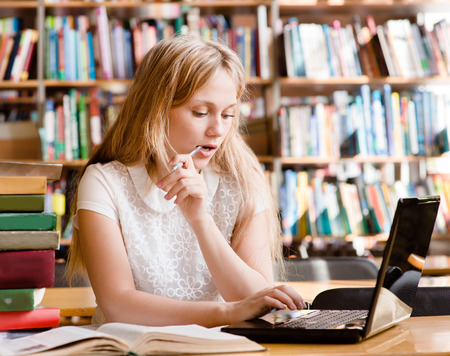 serious girl typing on notebook in library photo