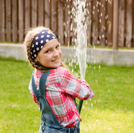 woman squirt: Happy cute little girl pouring water from a hose