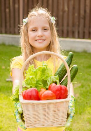 young girl holding basket of vegetables and looking at camera photo