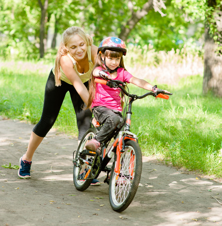 happy mother teaches his daughter to ride a bike photo