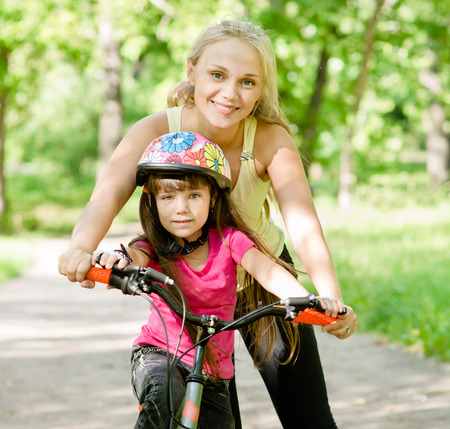mother and daughter learning to ride a bicycle photo