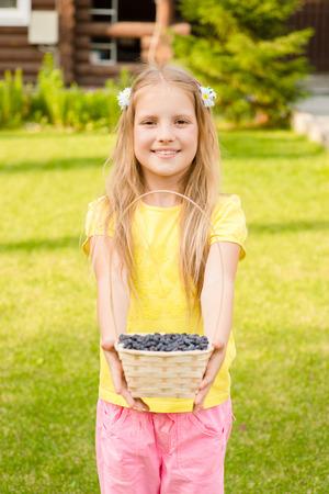 honeysuckle: teen girl holding basket with berry Stock Photo