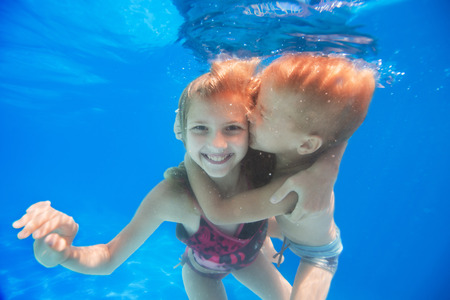 brother hugs and kisses his sister under water photo