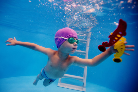 child dives into the pool for a toy photo