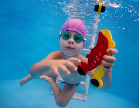 little boy trains in the pool to catch the toy under water photo