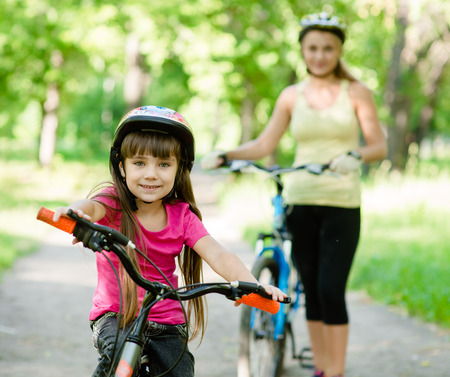 weekend activities: mom and daughter ride bikes in the forest