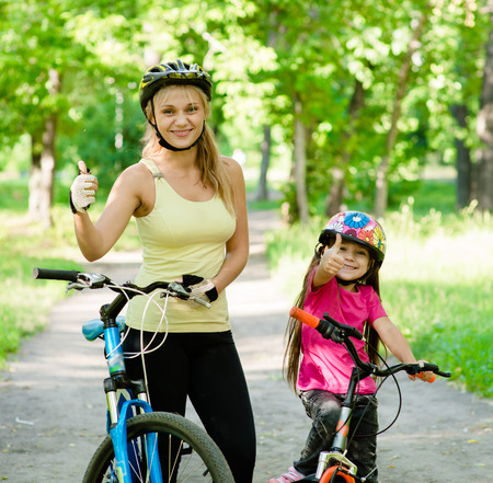 happy mother and daughter having fun, riding a bicycle and showing thumbs up photo