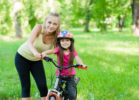 portrait of a happy mother embracing daughter who learns to ride a bike photo