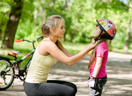 young mother dresses her daughter s bicycle helmet