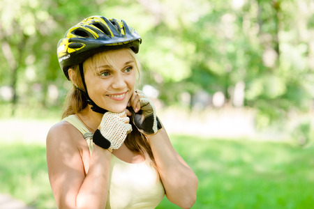 woman putting biking helmet on outside during bicycle ride photo