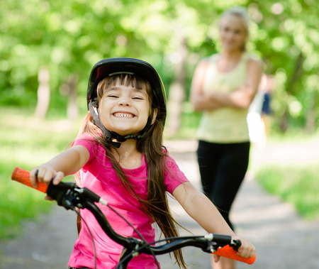teaching adult: Portrait of a little girl riding her bike ahead of her mother