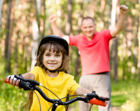 weekend activities: happy father rejoices that her daughter learned to ride a bike