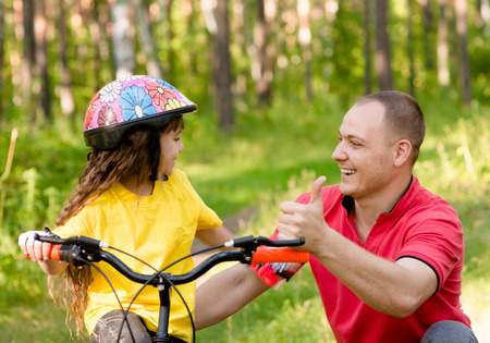 father praises his daughter, who learned to ride a bike photo