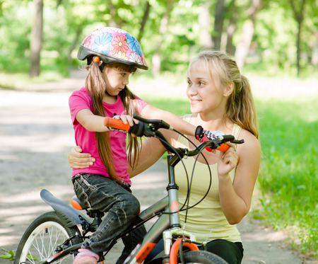 young mother calms the sad daughter who did not get to ride a bike photo