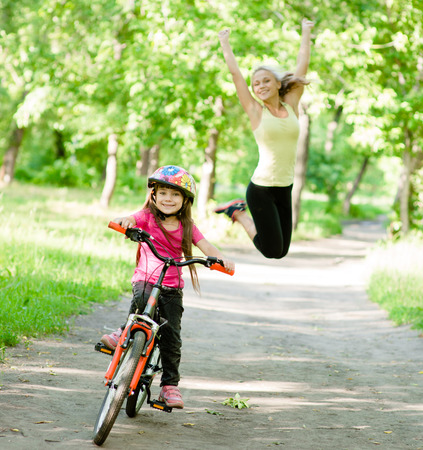 happy mother rejoices that her daughter learned to ride a bike photo