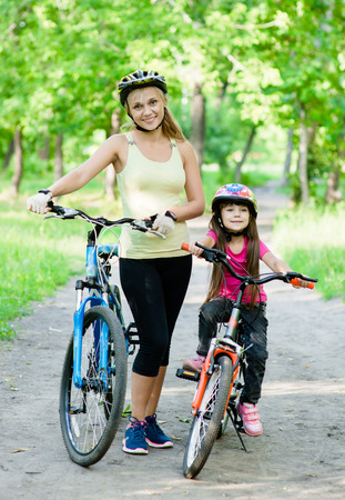 mom and daughter ride bikes in the park photo