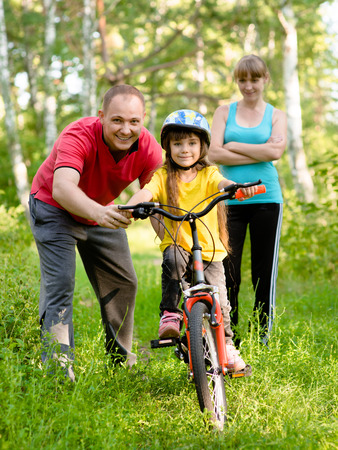 father teaches his daughter to ride a bike photo
