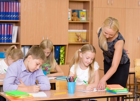 small group: Teacher helps the schoolkids with schoolwork in classroom Stock Photo