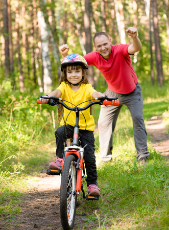 rejoices: happy father rejoices that her daughter learned to ride a bike