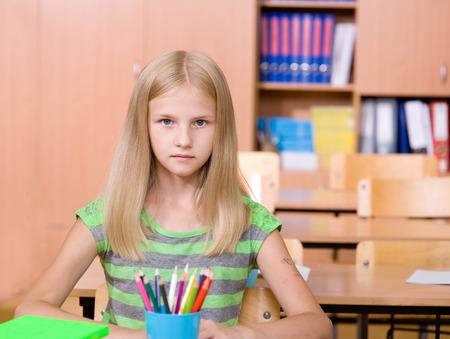 schoolgirl in classroom  looking at camera