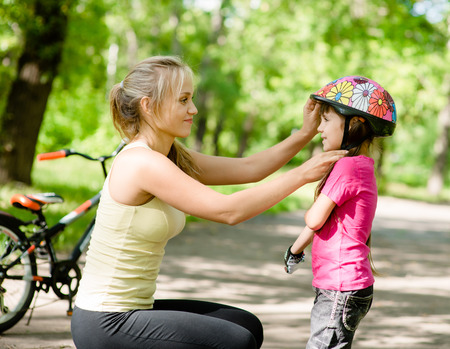 young mother dresses her daughter s bicycle helmet photo
