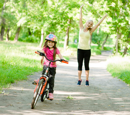children learning: happy mother rejoices that her daughter learned to ride a bike Stock Photo
