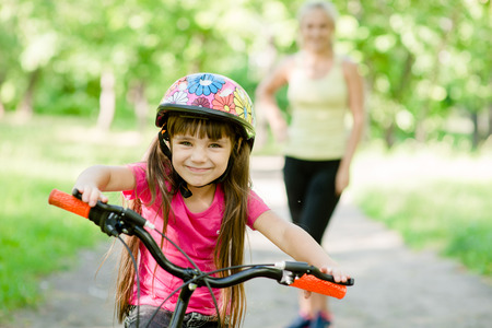 teaching children: mom and daughter ride bikes in the forest