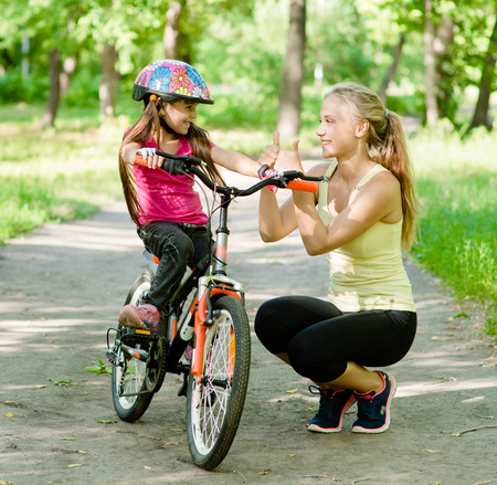 young mother praises her daughter, who learned to ride a bike photo