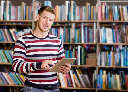 computer science class: Happy male student using a tablet computer in a library