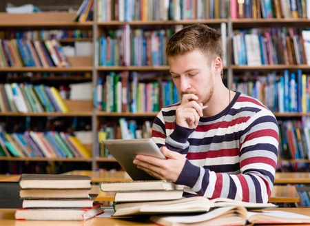 Étudiant pensive avec tablette pc à la bibliothèque Banque d'images