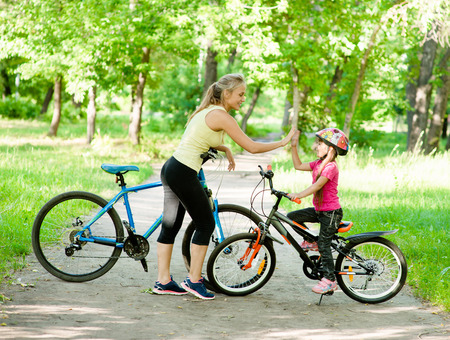 cycle ride: Mom and daughter give high five while cycling in the park