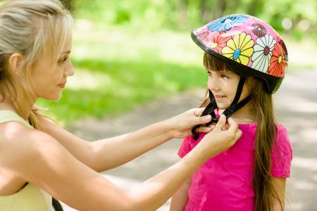 Młoda matka ubiera kask rowerowy córki Zdjęcie Seryjne