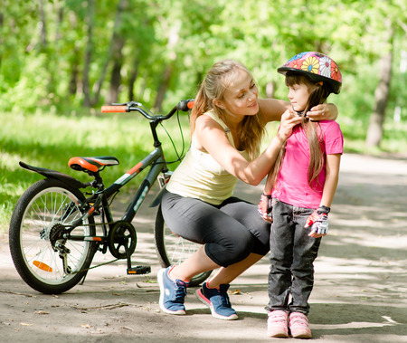 young mother dresses her daughters bicycle helmet Stock Photo