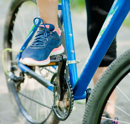 close up female foot on pedal of bicycle photo