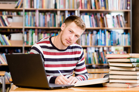 student with laptop studying in the university library photo
