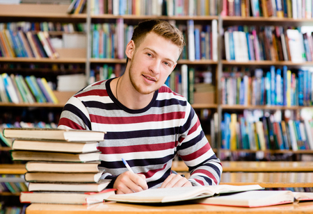 Smiling male student with open book working in a library photo