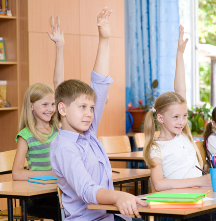 knowing: Children raising hands knowing the answer to the question
