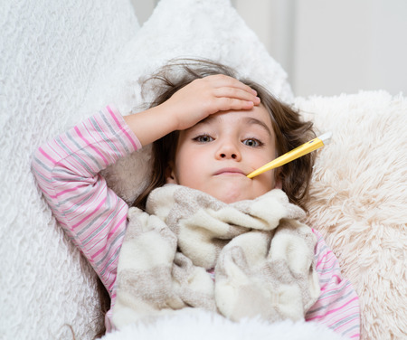niña enferma en la cama con un termómetro en la boca y toca la frente Foto de archivo
