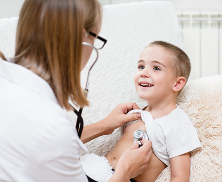 doctor examining boy with stethoscope photo