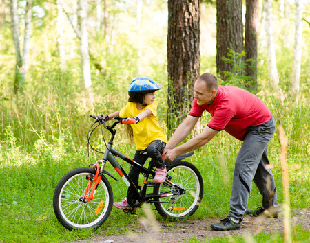 father teaching daughter: father teaching his daughter to ride a bike