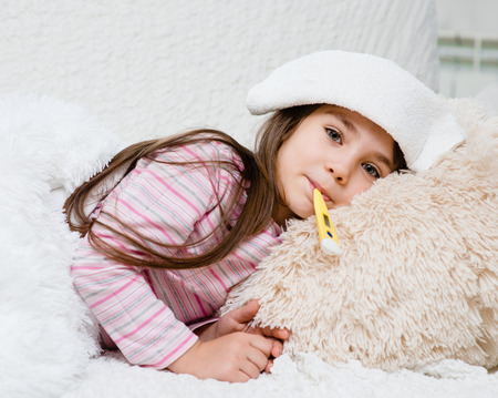 fever: sick girl lying in bed with a thermometer in mouth