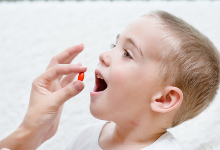 Child receiving pill - closeup photo
