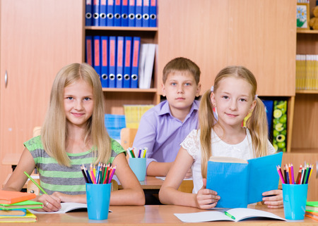happy students sitting at their desks in the classroom photo