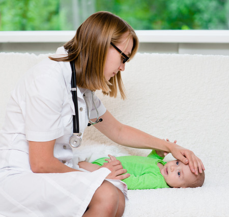 forehead: doctor checks the temperature of baby touching his forehead