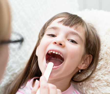 little girl having his throat examined by health professional photo