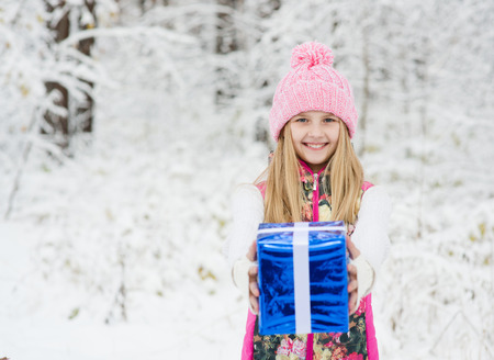 blonde girl  with gift in winter forest photo
