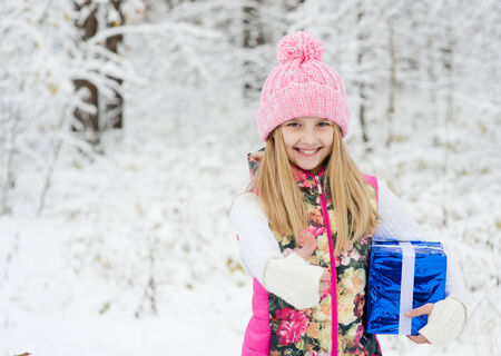 little girl with gift box showing thumbs up in winter forest photo