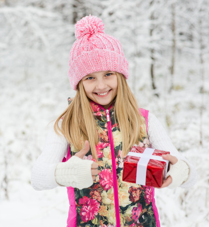 happy girl with red gift box showing thumbs up photo